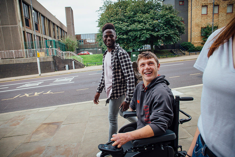 Blog featured image: a smiling young man in a power chair with his friends